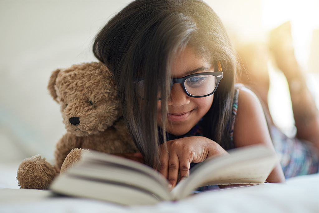 Young girl wearing glasses and reading a book - Pediatric Vision Care